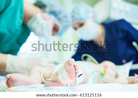 Neonatal Resuscitation. Doctor's team doing intensive therapy to newborn baby Stock photo ©