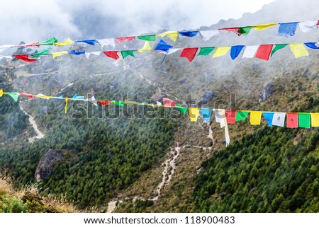 Nepal and and tibetan colorful prayer flags in mountains. Namche Bazaar valley in Himalayas. - stock photo