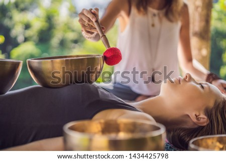 Nepal Buddha copper singing bowl at spa salon. Young beautiful woman doing massage therapy singing bowls in the Spa against a waterfall. Sound therapy, recreation, meditation, healthy lifestyle and