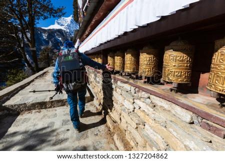 Nepal. Everest trekking. Tibetan prayer wheels in Boudhanath. In the frame of a man rotating the wheels. On wheels hieroglyphs - prayers in Nepali. Om mani padme hum - jewel in the lotus.