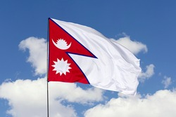 Nepal flag isolated on the blue sky with clipping path. close up waving flag of Nepal. flag symbols of Nepal.