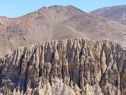 Nepal rocky cliffs Dhakmar with man made human cave dwellings in Himalayan mountains Upper Mustang region. Unique geological formations in Himalayas.