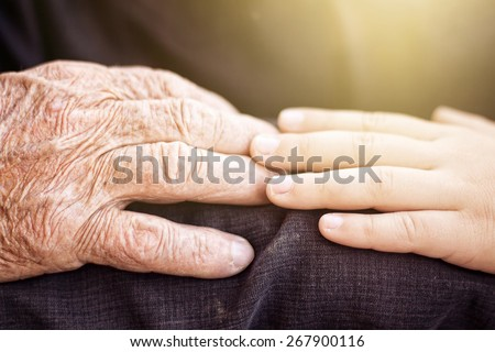 nephew touching grandfather\'s hand in sunlight