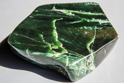 Nephrite macro photography of natural mineral  - piece of green Nephrit (jade) stone from geological collection