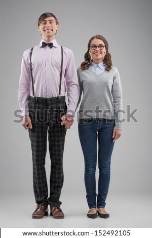 Nerd couple. Full length of happy nerd couple standing isolated on grey