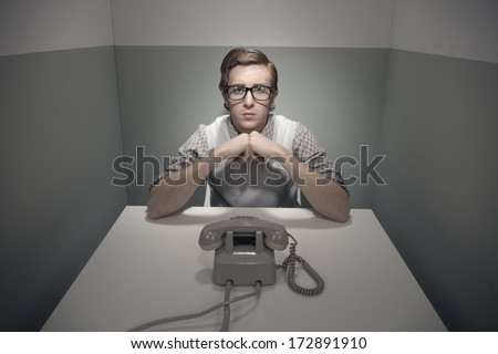 Nerd guy waiting for an important phone call in his small room.