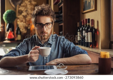 Nerd hipster guy with glasses sitting at bar table and using a tablet