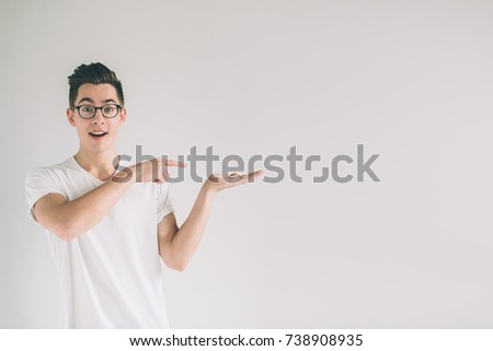 Nerd is wearing glasses holding something imaginary in one hand i. Man solated on white background. #738908935