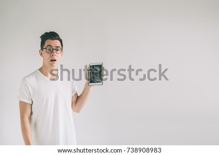 Nerd is wearing glasses. Student presenting a broken black tablet behind glass. upset man holds a out-of-use tablet or smartphone. Isolated on a light background. Broken screen