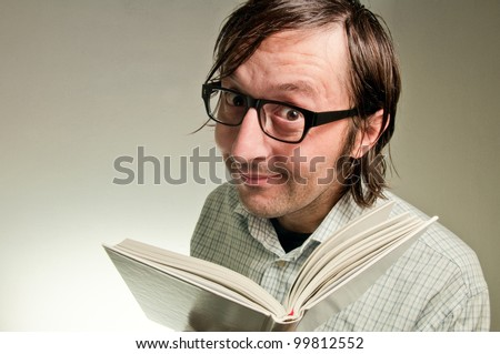 Nerd male holding a book with empty white covers, this image is a humorous concept photo. - stock photo