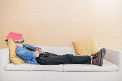 Nerd man sleep on sofa with book cover his face, sleep late reading book prepare for exam. Lifestyle education concept