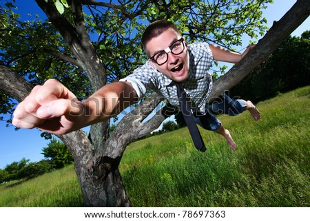 Nerd man thinking that he is superhero on the tree
