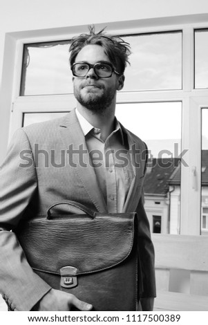 Nerd or brainiac wearing classic jacket. Education and work concept. Serious man or professor, teacher or worker with beard and messy hair in nerd glasses. Man with briefcase on glass door background.