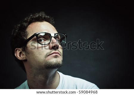 Nerd young  guy wearing white t-shirt against a gray background