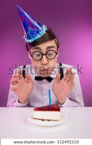 Nerds birthday. Young cheerful nerd man in glasses sitting at the table with a birthday cake on it