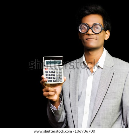 Nerdy asian accountant or maths genius wearing glasses and suit holding calculator isolated on dark background