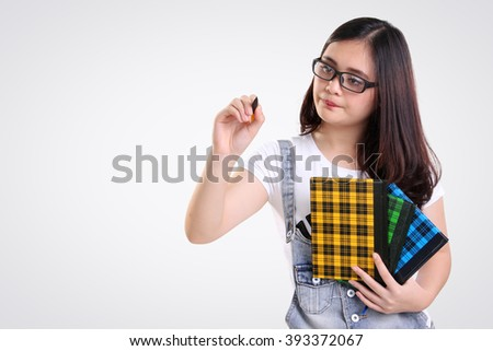 Nerdy female student gestures writing on the screen with a pen, isolated on white background