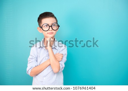 Nerdy young boy isolated in blue. Handsome early teenage boy portrait. confident looking pose.