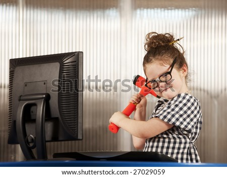Nerdy young girl smashing her computer with a hammer