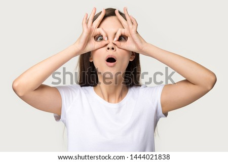 Nerdy young woman having fun making glasses shape with hands. Headshot of dummy millennial female do funny face with eyes wide open in studio isolated on grey background. People emotions concept