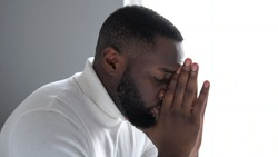 Nervous african american man going through difficult period in life, praying