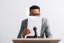 nervous african american speaker hiding behind paper during business conference