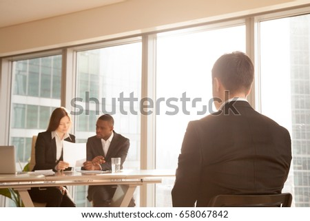 Nervous applicant sitting on chair waiting for result after job interview, worried businessman awaits for approve reject decision while expert group considering claim application complaint, rear view