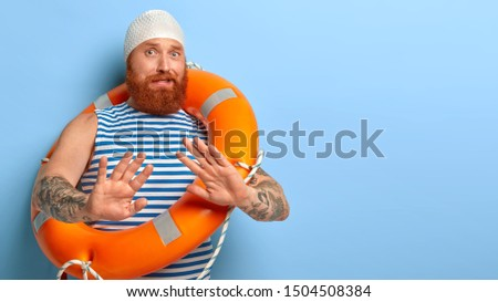 Nervous bearded ginger guy makes refusal gesture, palms outstretched afraids of swimming by himself without help learns swim wears waterproof headgear striped vest carries orange inflated lifebuouy