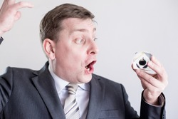 Nervous businessman in suit holds in hands drop of black oil of Brent brand, screams and shouts. OPEC.Crystal cube. Crisis in financial market, falling and rising prices, quotes, exchange rate changes