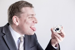 Nervous businessman in suit holds in hands drop of black oil of Brent brand, screams,shows tongue.Crystal cube. Crisis in financial market, falling and rising prices, quotes, changes in exchange rate.