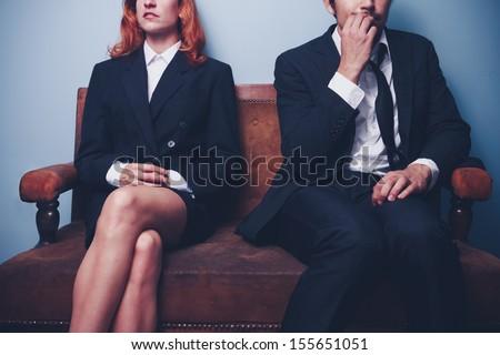 Nervous businessman sitting next to confident businesswoman #155651051