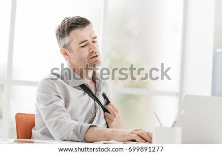 Nervous businessman working in a very hot office, he is sweating and loosening his tie
