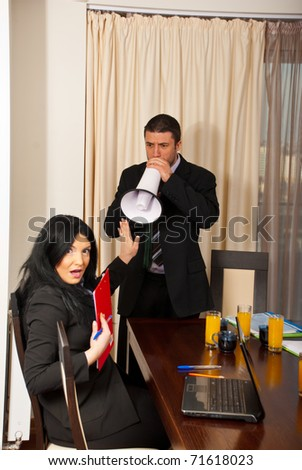 Nervous chief man with megaphone shouting to amazed business woman with stop hand