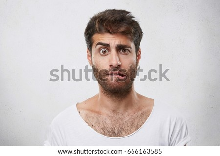 Nervous doubtful male with stylish hairstyle and beard frowning his eyebrow, biting lips having puzzled look going to make serious decision. Surprised macho man expressing his feelings and emotions
