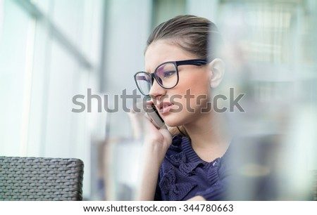 Nervous girl on mobile phone. Frowning young woman talking on telephone, something is wrong, problem.