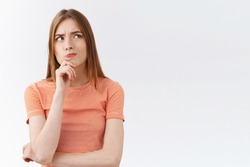Nervous girl trying find way how solve troublesome situation, touch chin thoughtful, look away serious and worried, pondering decision, making important choice, standing white background