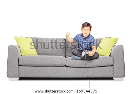 Nervous kid sitting on sofa and playing video games, isolated on white background