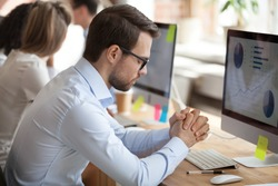 Nervous male millennial worker working at computer in shared office, trying keep calm not pay attention to problems, worried employee meditate at workplace staying patient, controlling emotions