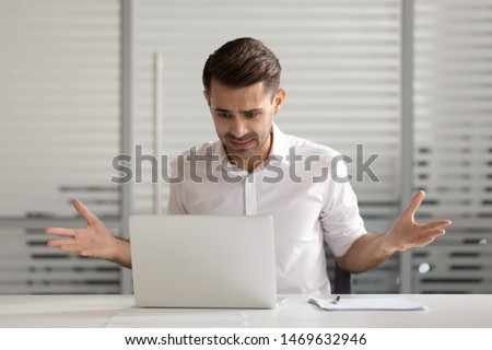 Nervous male worker sit at office desk feel confused having operational software problems at laptop, frustrated man employee panic experience virus attack or computer breakdown and data loss