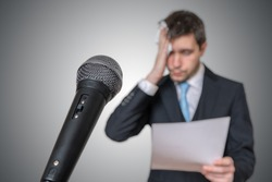 Nervous man is afraid of public speech and sweating. Microphone in front.