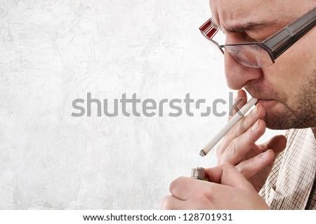 Nervous man lighting a cigarette. Smoking addiction concept.