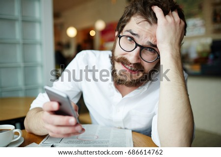 Nervous man with smartphone seeking for job