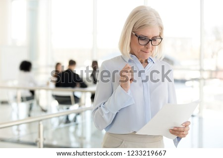 Nervous middle aged old businesswoman feeling scared stressed afraid waiting for job interview, worried mature senior applicant or speaker reading papers preparing for public speaking fear concept