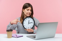 Nervous unhappy woman office worker pointing finger at display of wall clock talking video call on laptop sitting at workplace, time to break. Indoor studio shot isolated on pink background
