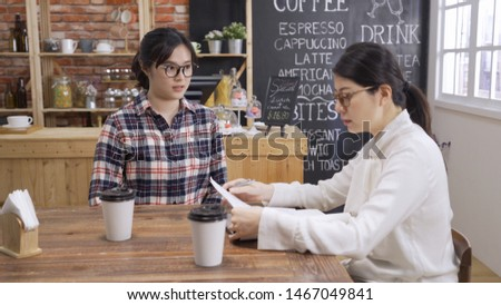 Nervous woman candidate in eyeglasses look at manager reading resume during job interview in cafe bar. applicant with worriment human resources generalist. fresh graduate giving application vacancy