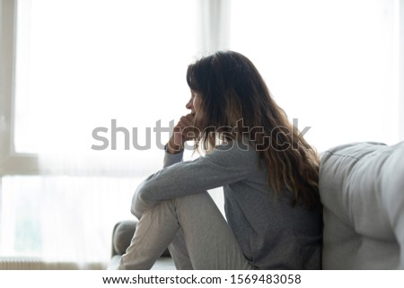 Nervous woman seated on couch lost in sad thoughts about divorce, break up or separation with husband. Addicted female need psychological help therapy in rehab concept of alcohol or drug dependence