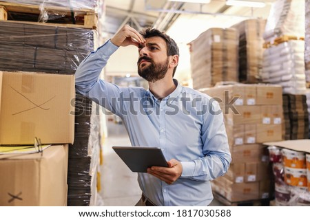 Nervous young attractive bearded businessman leaning on box in warehouse, holding tablet and thinking about problem while holding his head.