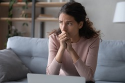 Nervous young woman sitting on sofa, worrying about bad news, received by email on laptop. Stressed businesswoman thinking of crisis challenges, feeling desperate or unsure, stack with hard decision.