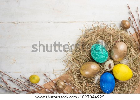 Nest with Easter eggs on a wooden background, top view with copy space #1027044925