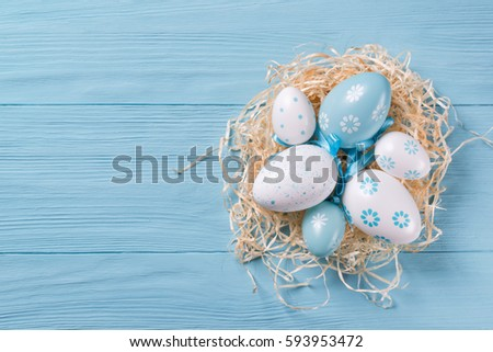 Nest with Easter eggs on blue wooden background, top view with copy space #593953472